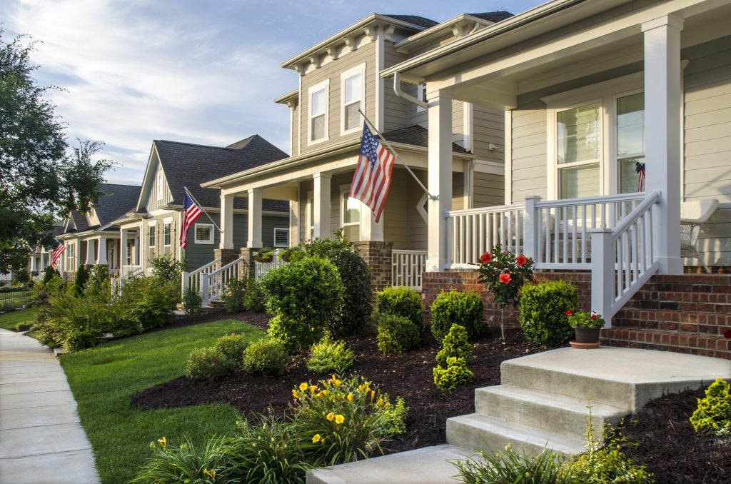 Belmont, North Carolina, USA - June 19, 2016: The American Dream is pictured in this iconic image of the front of a traditional, Victorian-style homes in the Eagle Park neighborhood development. Eagle Park reflects the new style of neighborhoods where homes are built on smaller lots with amenities such as parks, pools and located near small towns and large cities. An American flag hangs from the front porch in celebration to honor an upcoming holiday. Many Americans express patriotism by flying Old Glory, not only on holidays, but all year long. The architecture reflects old styles, however, the construction of the homes has used modern materials and finishes.