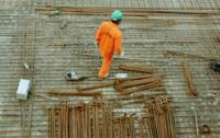 A construction worker in a green hard hat and orange jumpsuit on the worksite.